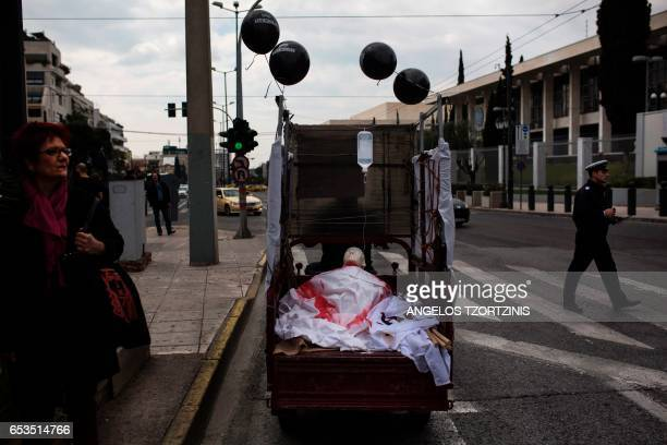 TOPSHOT People walk next to a mannequin carried on the back of a vehicle during a demonstration against austerity measures in Athens on March 15 2017...