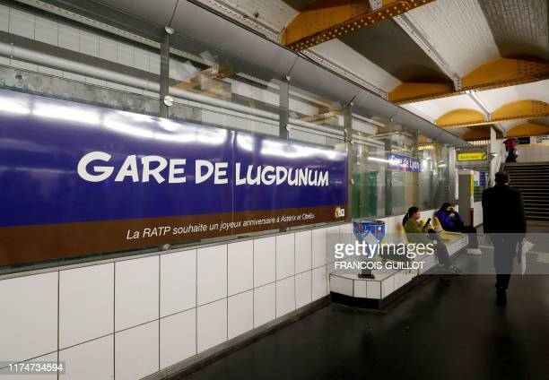 People walk next to a metro station sign especially designed to commemorate the 60th anniversary of France's famous comic characters Asterix and...