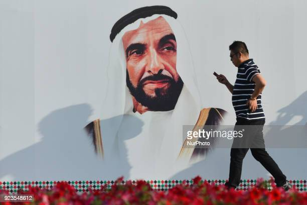 People walk next to a mural with an image of Sheikh Zayed bin Sultan Al Nahyan the principal driving force behind the formation of the United Arab...