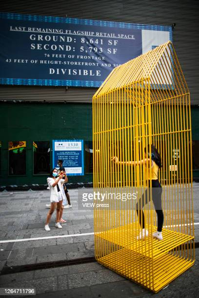 People walk next to a poster of a retail space to rent in Times Square on August 8 2020 in New York City With more than four months NYC has closed...