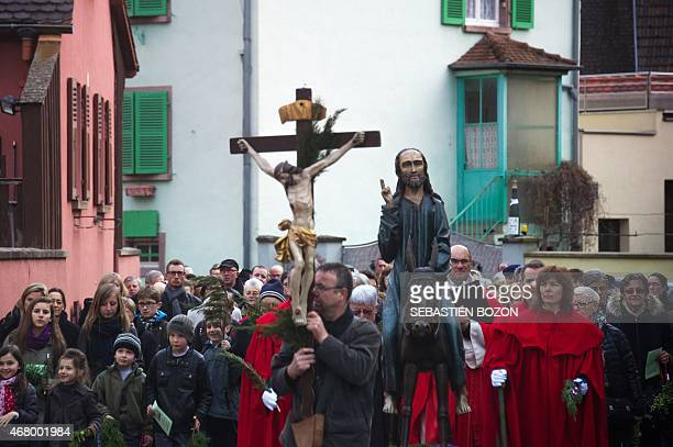 People walk next to a wooden statue of Jesus riding a donkey through the village of Ammerscwhir on March 29 2015 During the Palm Sunday procession...