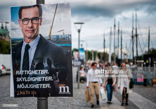 People walk next to an election poster of Ulf Kristersson leader of the Moderate Party in Sweden on September 1 2018 in Stockholm The general...
