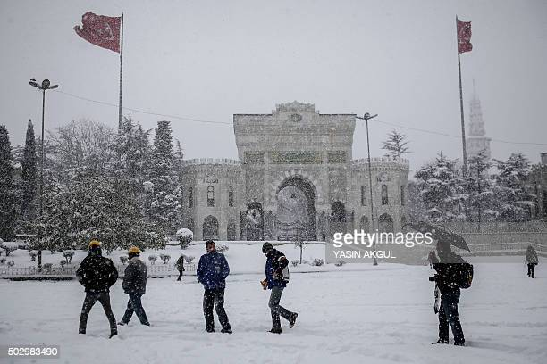 People walk next to an university during a snowfall in Istanbul on December 31 2015 Istanbul governors office has urged people to avoid going outside...
