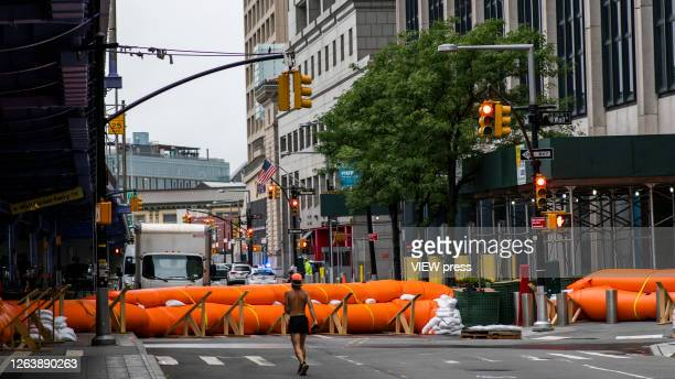 People walk next to flood barriers used to prevent flooding at the South Street Seaport as the city gets ready for tropical storm Isaias on August 4...