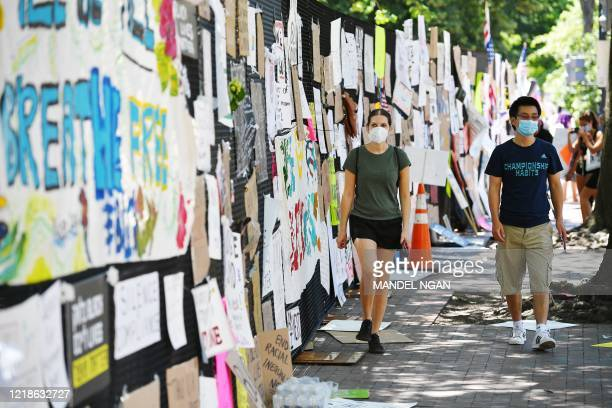 People walk next to placards and posters attached to a security fence on the north side of Lafayette Square, near the White House, in Washington, DC...