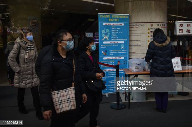 People walk next to signage detailing hygenic practices to prevent the spread of a SARSlike coronavirus at the Huashan Hospital in Shanghai on...