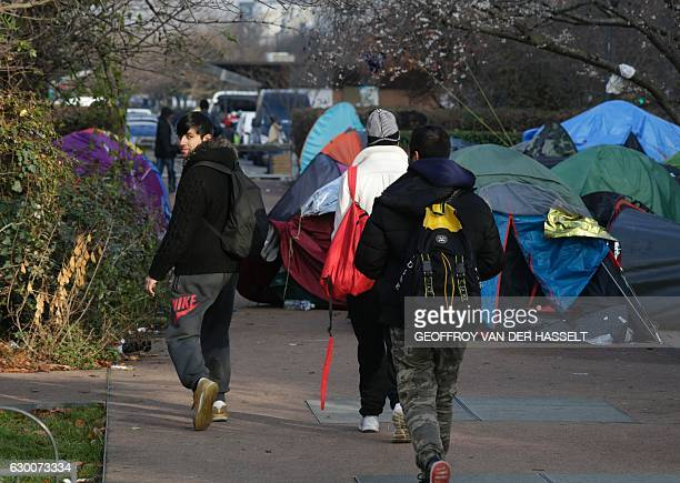 People walk next to tents during the dismantling of a makeshift camp set by migrants, on December 16, 2016 in Saint-Denis, a northern Paris' suburb....