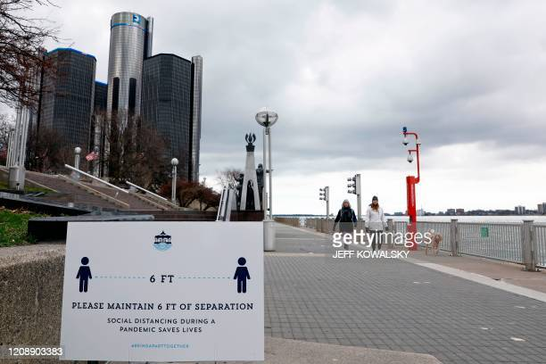 People walk next to the Detroit River in Detroit, Michigan on April 1, 2020.