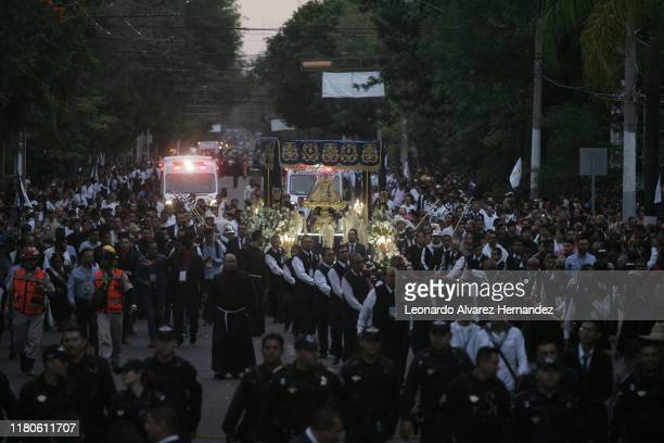 People walk next to the religious image of the Virgin of Zapopan during the annual celebration of 'La Romeria' on October 12, 2019 in Guadalajara,...