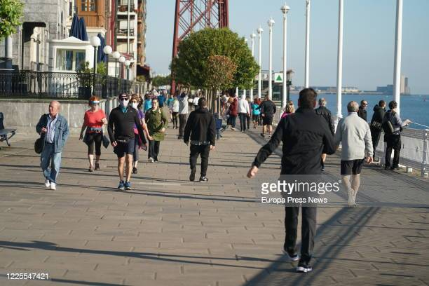 People walk next to the Vizcaya Bridge, also known as the Bizkaia Bridge, which joins the two banks of the Bilbao estuary in Vizcaya and links the...
