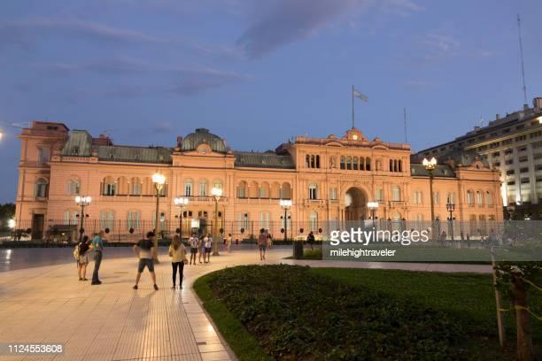 People walk nighttime sidewalk Plaza de Mayo park Presidential Casa Rosada Buenos Aires Argentina