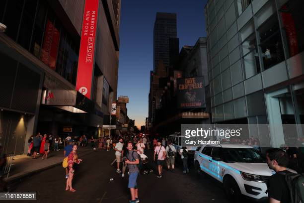 People walk on 46th Street in Times Square during a power outage that effected midtown and the west side of Manhattan on July 13 2019 in New York City