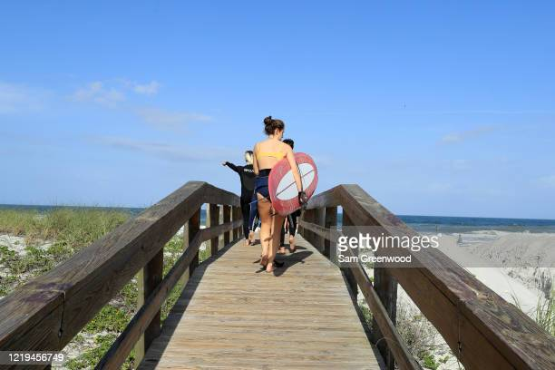 People walk on a beach access on April 17 2020 in Jacksonville Beach Florida Jacksonville Mayor Lenny Curry announced Thursday that Duval County's...