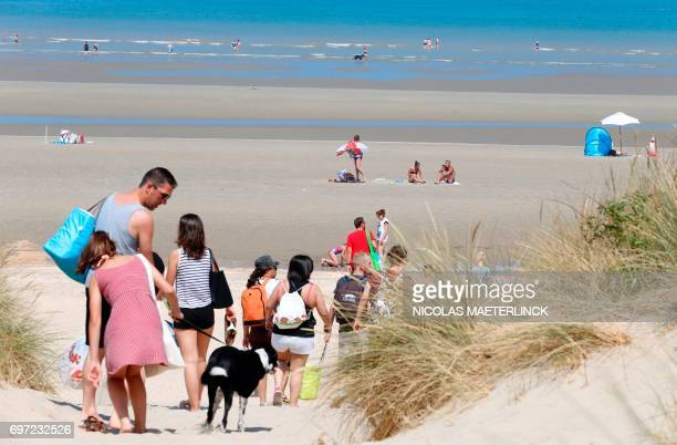 People walk on a beach in De Panne on the Belgian coast on a hot and sunny day on June 18 2017 / AFP PHOTO / BELGA AND Belga / NICOLAS MAETERLINCK /...