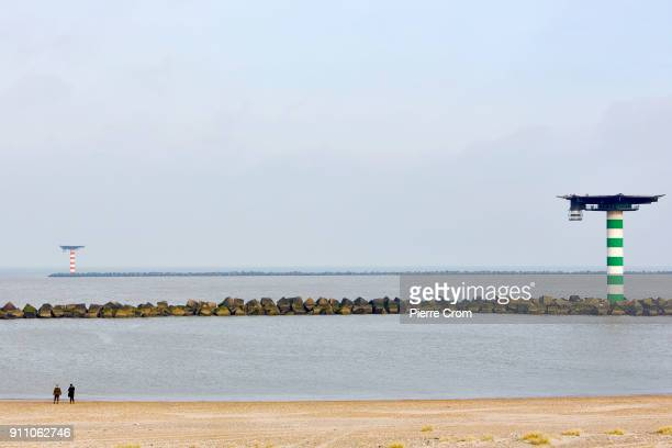 People walk on a beach in the Port of Rotterdam the largest port in Europe in Rotterdam on January 27 2018 Entrepreneurs working in the Port of...