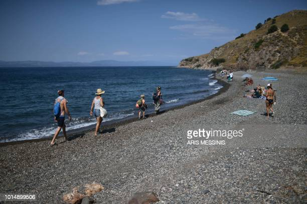 People walk on a beach near the village of Skala Sykamineas on the Greek island of Lesbos on August 3 2018