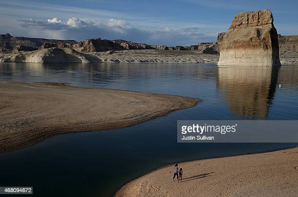 People walk on a beach the used to be the bottom of Lake Powell at Lone Rock Camp on March 29 2015 near Big Water Utah As severe drought grips parts...