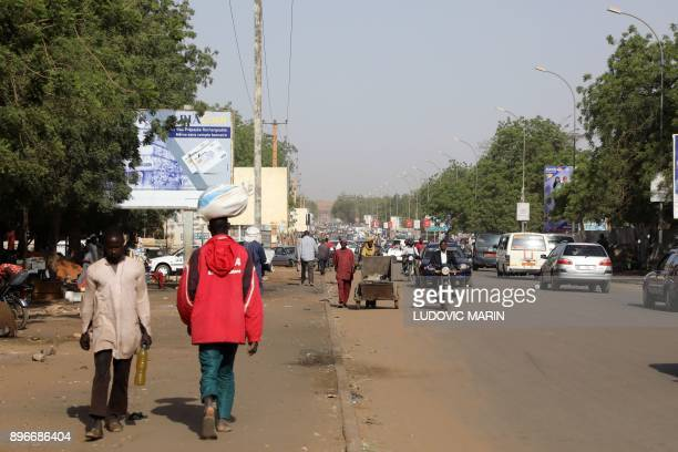 People walk on a boulevard in downtown Niamey on December 21 2017 / AFP PHOTO / LUDOVIC MARIN