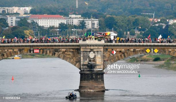 People walk on a bridge over the river Elbe as they take part in a demonstration titled Unteilbar against exclusion on August 24 2019 in Dresden...