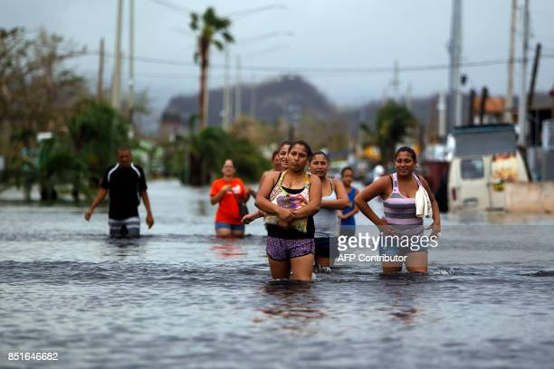 People walk on a flooded street in the aftermath of Hurricane Maria in San Juan Puerto Rico on September 22 2017 Puerto Rico battled dangerous floods...