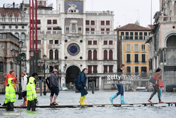People walk on a footbridge in the flooded St Mark's Square during a highwater alert in Venice on October 29 2018 The flooding caused by a...