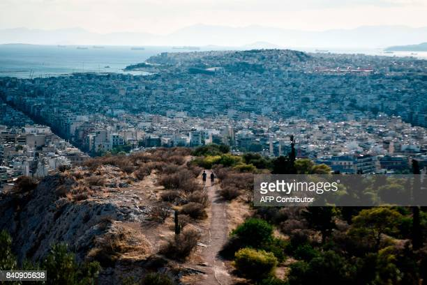 People walk on a hill overlooking Athens and the Piraeus on August 30 2017 / AFP PHOTO / LOUISA GOULIAMAKI