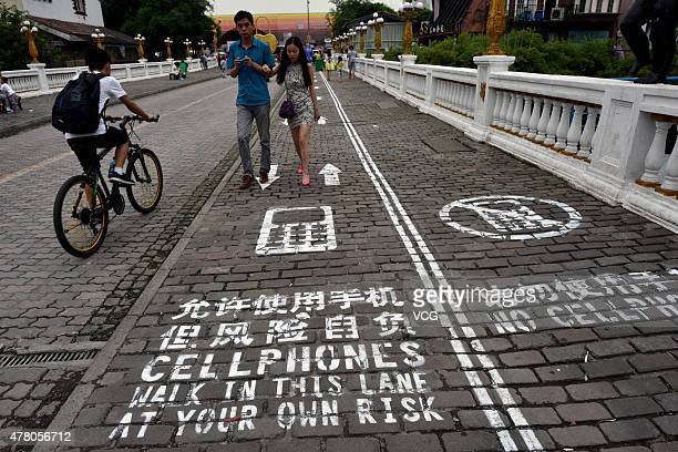 People walk on a 'mobile sidewalk' which dedicated to mobile phones tells pedestrians 'Walk in this lane at your own risk' at the Foreigners Street...
