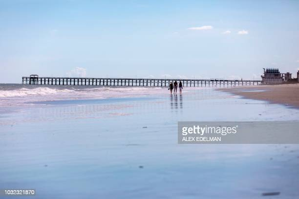TOPSHOT People walk on a nearly empty beach in Myrtle Beach South Carolina on September 12 2018 Hurricane Florence was downgraded to a Category 3...
