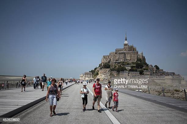 People walk on a newly opened footbridge that leads to MontSaintMichel northwestern France on July 22 2014 AFP PHOTO / CHARLY TRIBALLEAU