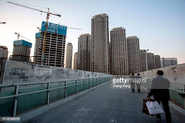 People walk on a overpass beside a huge construction site Due to blind interventions by the government in the past years though prices increased in...