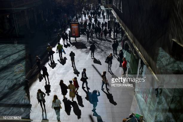 People walk on a pedestrian street in the central business district of Sydney on August 7 2018 Australia's population will reach the 25 million mark...