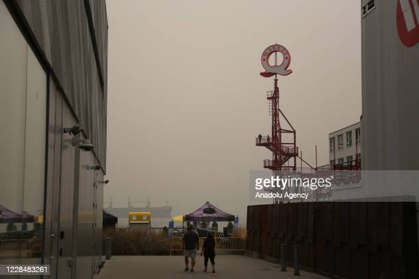 People walk on a pier at Lonsdale Quay Market as smoke from wildfires fills the air in North Vancouver, British Columbia, Canada on September 12,...