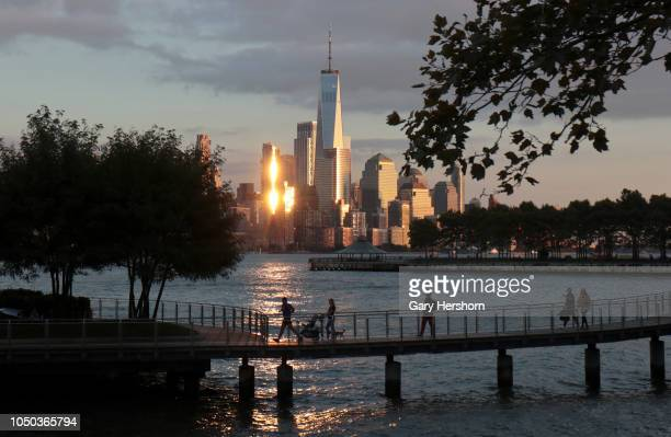 People walk on a pier in front of the skyline of lower Manhattan and One World Trade Center in New York City at sunset on October 3 2018 as seen from...