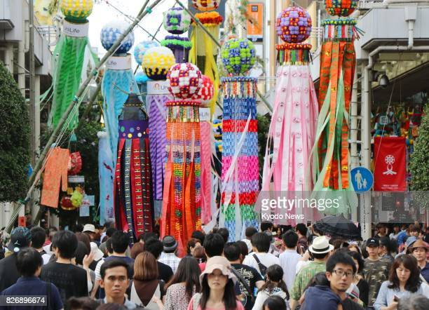 People walk on a shopping street in the northeastern Japan city of Sendai under colorful streamers of the Tanabata star festival on Aug 6 the opening...