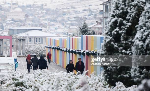 People walk on a sidewalk after season's first snowfall in Usak, Turkey on November 21, 2017. Snow depth reaches 3 centimeters in town center and 10...