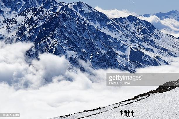 People walk on a slope at the Oukaimeden ski resort in the Atlas Mountains 30 kilometres from the popular tourist resort of Marrakesh on February 17...