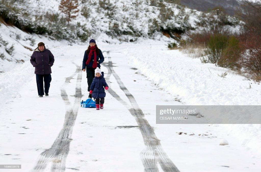 People walk on a snow-covered road in Pineda de la Sierra, near Burgos, on January 23, 2013.