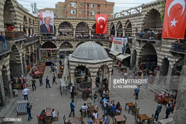 People walk on a square under hanging posters of Turkish President Recep Tayyip Erdogan and Tukish national flags in the historical Sur district in...