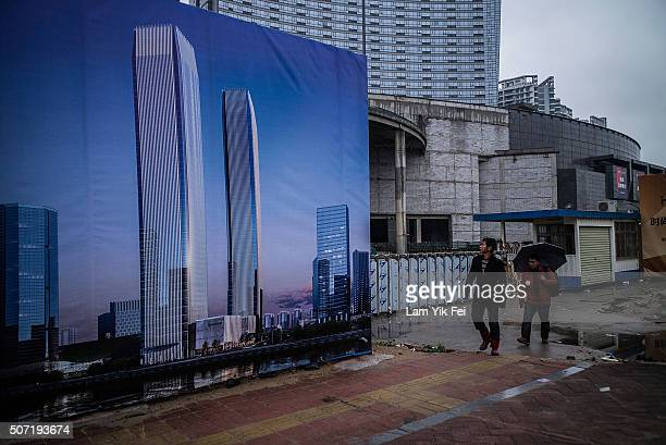 People walk on a street at Houjie town on January 27 2016 in Dongguan China China's slowing economy and falling stock market have caused concerns for...