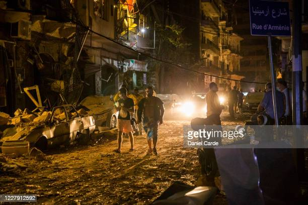 People walk on a street covered in debris after a large explosion on August 4, 2020 in Beirut, Lebanon. There was a structure fire near the port of...