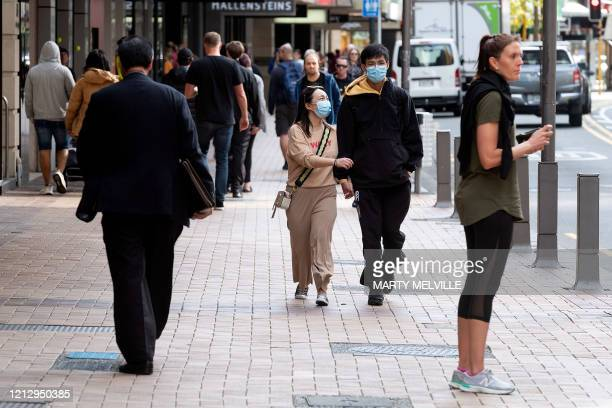 People walk on a street in Wellington on May 14, 2020. - New Zealand will phase out its coronavirus lockdown over the next 10 days after successfully...