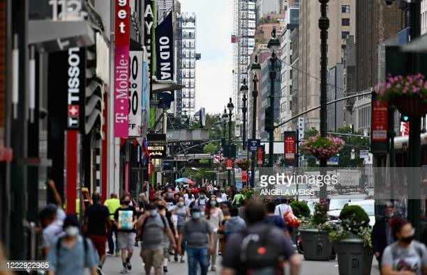 People walk on a street near Herald Square on June 25, 2020 in New York City. - New York businesses opened their doors to returning waves of workers...