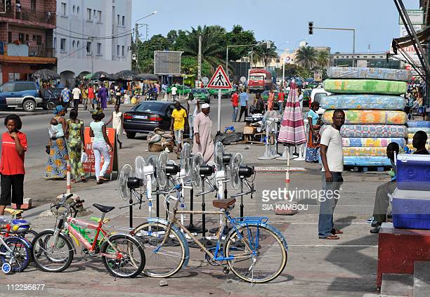 People walk on a street of Koumassi district southern Abidjan where some shops are open on April 18 2011 Ouattara's government ordered civil servants...