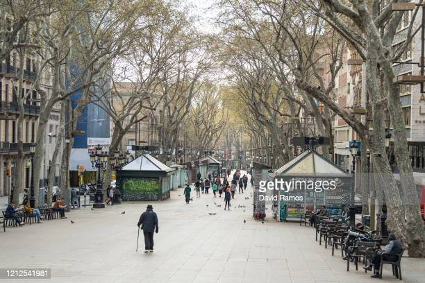People walk on an unusually empty Las Ramblas on March 15, 2020 in Barcelona, Spain. As part of the measures against the virus expansion the...