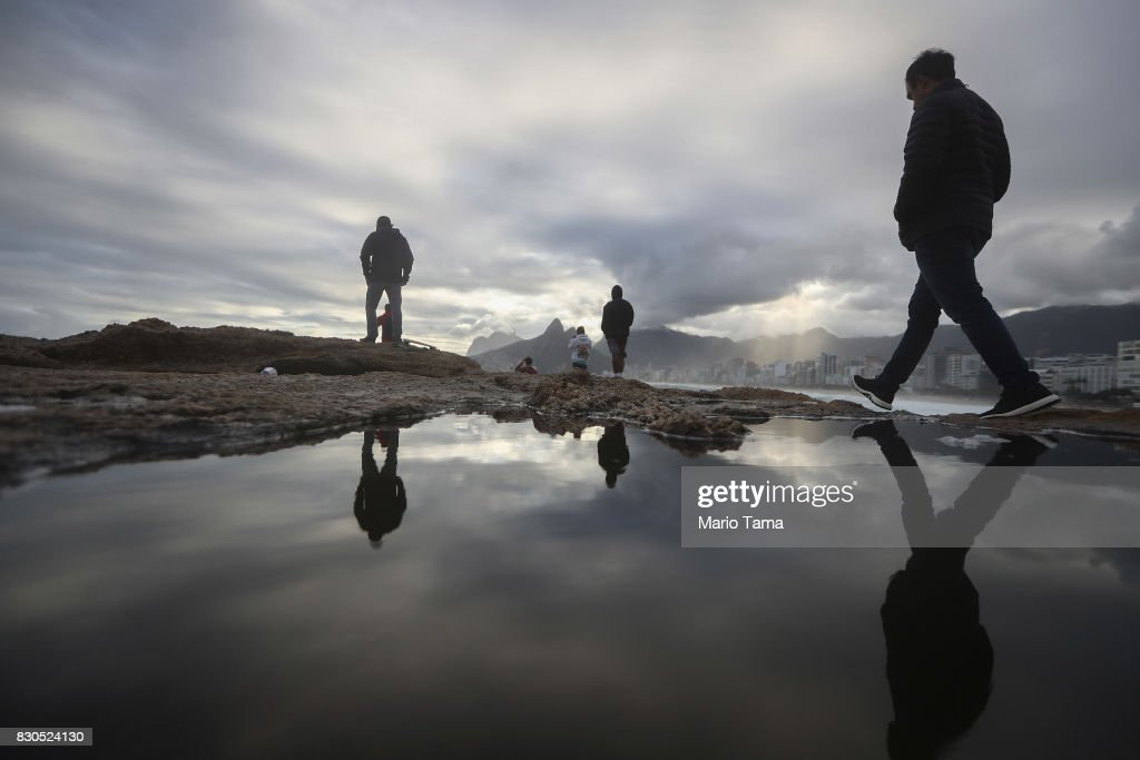 People walk on Arpoador rock during strong winter swells on the Atlantic Ocean on August 11, 2017 in Rio de Janeiro, Brazil. Waves were measured as high as thirteen feet in Rio today in the middle of Brazil's winter season. According to the Urban Climate Change Research Network (UCCRN), Rio's average temperature would rise around one degree Celsius between 2015 and 2020 along with a sea level rise of 14 cm. Changes in Rio's climate are projected to be the most dire of all cities in South America, according to UCCRN.