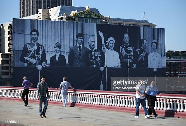 People walk on Blackfriars Bridge in sight of a giant photograph of The British Royal family on a building on The River Thames on May 25 2012 in...