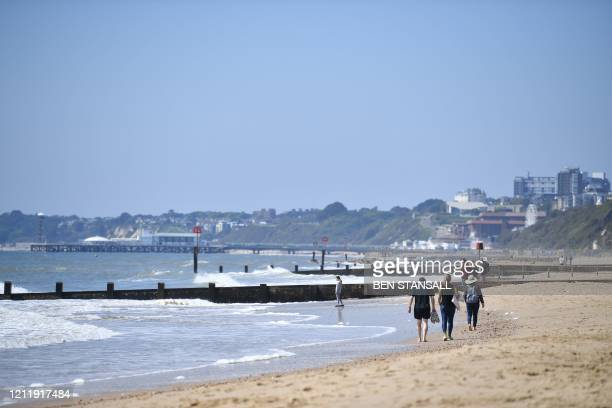People walk on Boscombe beach in Bournemouth, southern England, on May 6, 2020 as life continues under a nationwide lockdown imposed to slow the...