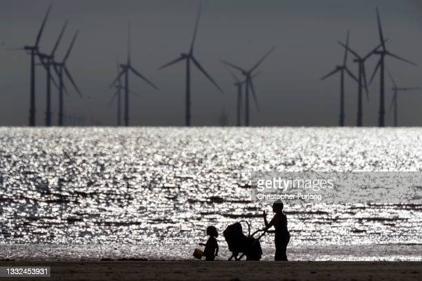 People walk on Crosby Beach near the Burbo Bank Offshore Wind Farm on August 04, 2021 in Liverpool, United Kingdom.