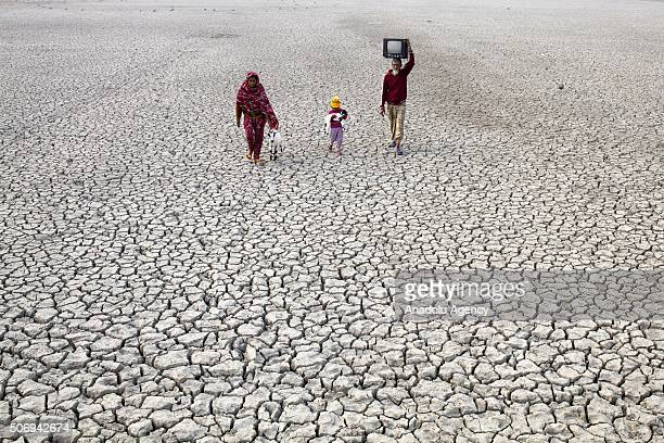 People walk on deep cracks field as rise of sealevel causes deep cracks by leaving salt on ground after evaporation in Satkhira Bangladesh on January...