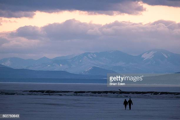 people walk on frozen lake champlain in burlington - burlington vermont stock photos and pictures